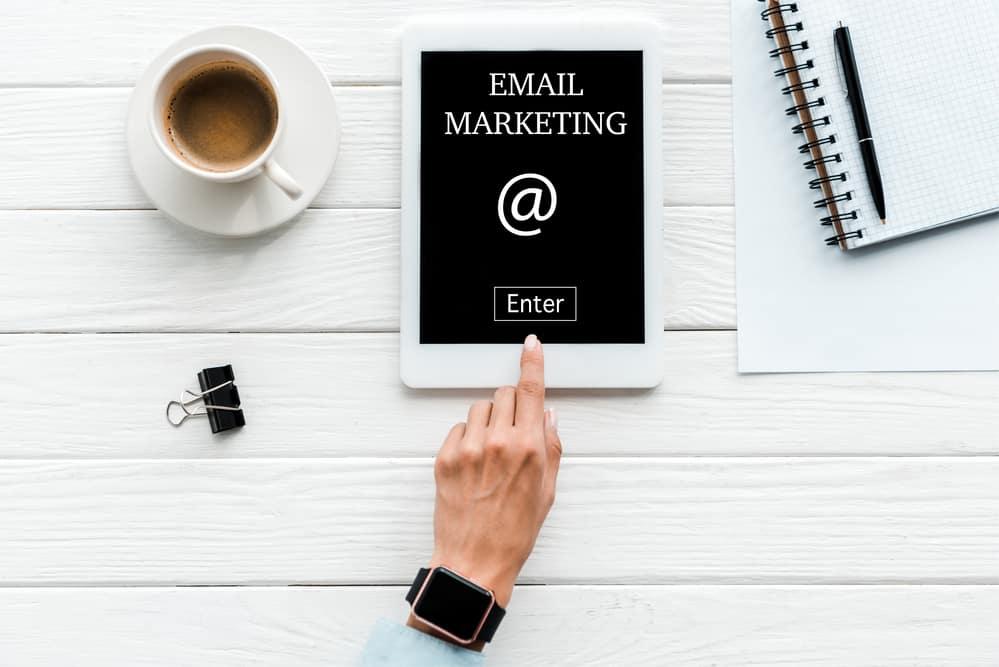 Afbeelding van een bureau met daarop een tablet met e-mail marketing